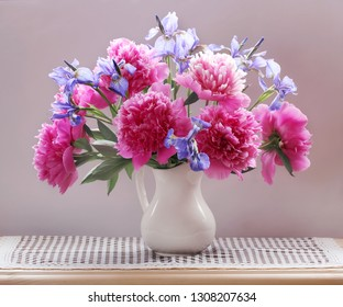 peonies and irises in a jug on the table. garden flowers, still life.