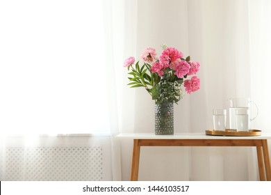 Peonies in vase and tray with jug and glasses of water on console table near wall, space for text. Room interior