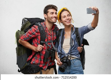 People, active lifestyle, relaxation and joy concept. Happy Caucasian couple of tourirsts reaching their destination, making selfie, smiling broadly into camera. Young hitchhikers photographing