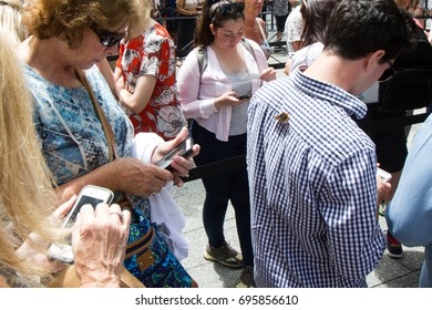 People addicted to their mobile or cell smart phones oblivious to the butterfly that's landed the on person's shoulder taken in a queue in Manhattan, New York, USA, circa July 2015