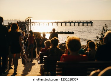 People admire the sunset on the sea pier. Palanga, Lithuania. Defocused