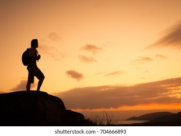 People adventure, and exploration concept. Male hiker backpacker standing on edge of mountain looking out at the view.
