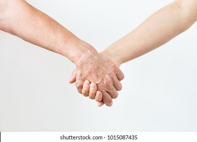 people, age and body parts concept - close up of senior and young woman holding hands