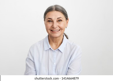 People, age, business and elegance. Attarctive cheerful gray haired mature businesswoman rejoicing at profitable contract, smiling happily. Senior female in blue shirt expressing positive emotions