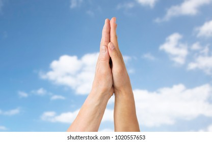 people, age and charity concept - close up of senior and young woman touching hands over blue sky and clouds background