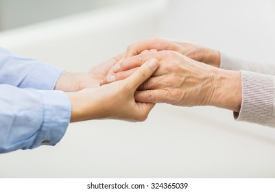 people, age, family, care and support concept - close up of senior and young woman  holding hands