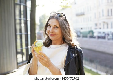 People, age, food and modern lifestyle concept. Attractive fashionable gray haired female in good mood spending nice summer day outdoors, posing against blurred city background with ice cream cone