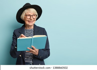 People, age, free time concept. Glad senior female on pension writes list to do in her blue notepad, smiles positively while looks with dreamy expression aside, wears formal apparel, stands indoor