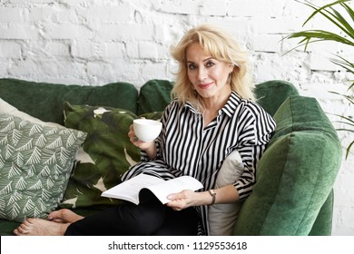People, age, leisure and hobby concept. Picture of beautiful middle aged housewife dressed in stylish elegant clothes sitting on sofa with mug and book, having morning coffee and reading novel