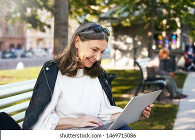 People, age, lifestyle, technology and communication. Outdoor image of beautiful retired female dressed in stylish clothes sitting on bench with touch pad pc on her lap, watching funny video, laughing