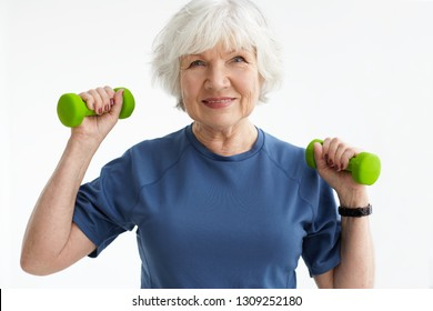 People, age, sports and active lifestyle concept. Picture of happy positive mature retired woman in t-shirt doing exercise with free weights in gym. Excited senior female training with dumbbells