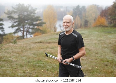 People, age, trekking, sports, adventure and hobby concept. Outdoor shot of unshaven sporty man pensioner with gray hair having excited happy look while exercising outdoors with nordic walking poles