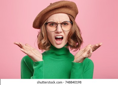 People, aggression, emotions concept. Angry annoyed woman wears retro outfit, gestures actively, has quarrel with colleagues who make her do all office work alone. Emotinal exasperate female