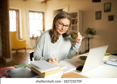 People, aging, retirement and occupation concept. Attractive sixty year old female teacher conducting online lesson sitting at desk at home in front of open laptop, making notes and drinking tea