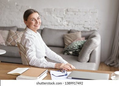 People, aging, technology, occupation and lifestyle concept. Indoor shot of cheerful beautiful senior businesswoman in white shirt working from home office, sitting at desk and smiling happily