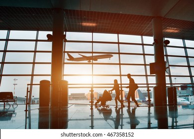 people in airport, silhouette of young family with baby traveling by plane, vacations