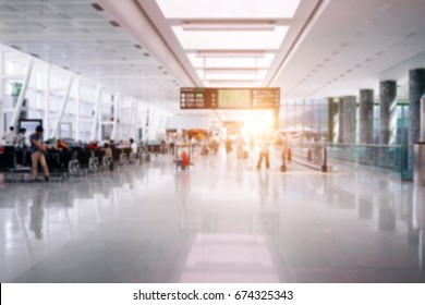 People in airport terminal,blurred background.