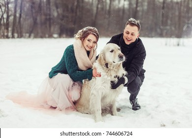 People, animal, love and leisure concept - happy couple laughing outdoors in winter with big dog. Couple embracing in snowy winter park.Stylish beautiful young couple bride and groom have fun with dog