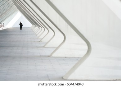 People in the architectural perspective. The sloping lines of the architecture. The man in the suit comes in a bright corridor in a modern building