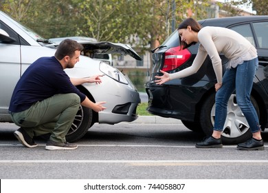 People arguing after a car crash and trying to find friendly agreement