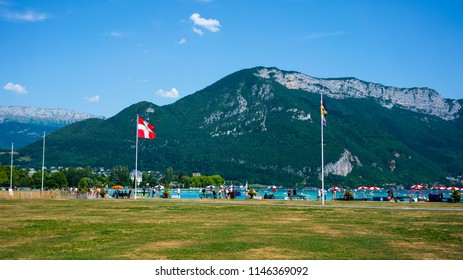 People around Annecy lake riverbank with Savoie region flag and Veyrier mount of Alps mountains in background