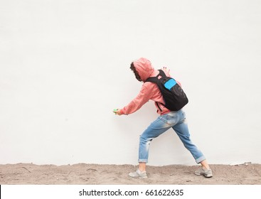 people, art, creativity and youth culture concept - young woman or teenage girl drawing graffiti with spray paint on street wall from back