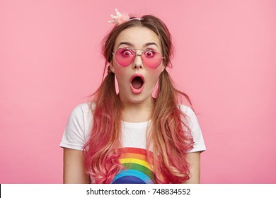 People, astonishment and disbelief concept. Adorable pretty attractive woman wears colorful clothes and accessories looks puzzled after reading awful comments from viewers on her social network site