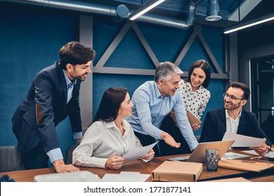 Teilnehmer an einem Geschäftstreffen in einem modernen offenen Planbüro während der Sitzung am braunen Schreibtisch