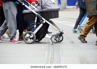 People, baby stroller, crossing street, close up of feet. Tram rails