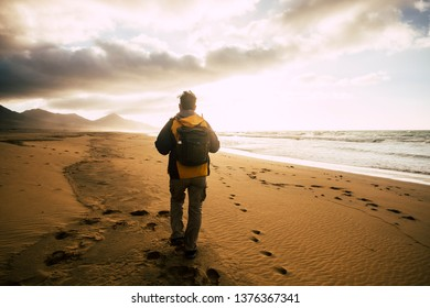 People in back view walking alone with his backpack on the desolation beautiful wild beach for alternative concept of tourism vacation - adventure and explore scenic place - freedom and feeling nature