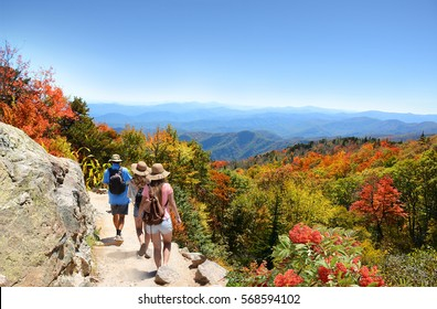 People with backpacks hiking on fall trip in mountains. Father with his family enjoying time on a trip. Close to Asheville, Blue Ridge Mountains, North Carolina, USA.