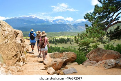People with backpacks hiking on summer vacation in mountains. Father with his family enjoying time on a trip. Blue sky and high mountains in background. Rocky Mountain National Park, Colorado, USA.