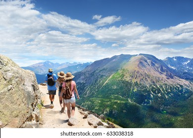 People with backpacks hiking on summer vacation in mountains. Father with his family enjoying time on a trip. Rocky Mountain National Park landscape. Colorado, USA.