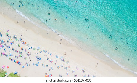 People bathing in the sun, swiming and playing games on the beach. Tourists on the sand beach, Aerial view of sandy beach with tourists swimming in beautiful clear sea water.