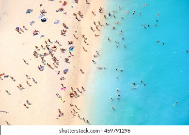 People bathing in the sun, swiming and playing games on the beach. Tourists on the sand beach of Navagio Zakynthos Greece.