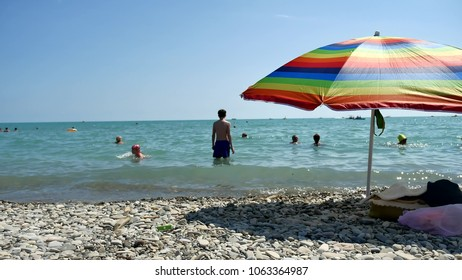 People bathing in the sun, swimming and playing games on the beach. Tourists on the beach from the pebbles sea ocean