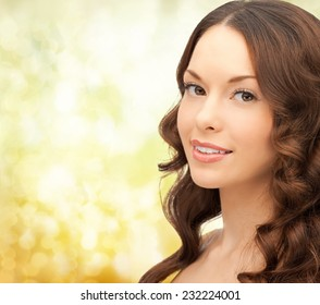 people and beauty concept - beautiful young woman over yellow lights background