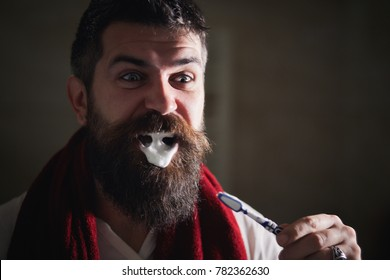 people and beauty concept - smiling young bearded man with toothbrush cleaning teeth. Portrait of brutal bearded man brushing teeth in the bathroom. The morning always starts with good oral hygiene.
