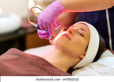 people, beauty, cosmetic treatment, cosmetology and technology concept - beautician with microdermabrasion device doing face exfoliation to young woman lying at spa