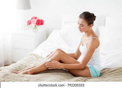 people, beauty, cosmetics, bodycare and spa concept - beautiful woman applying moisturizing cream to her legs at home bedroom