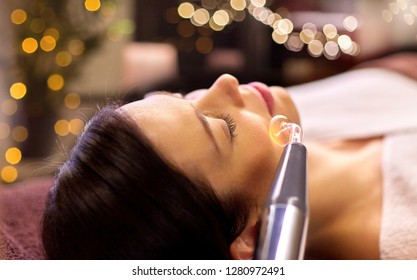 people, beauty, cosmetology and technology concept - beautiful young woman having needle free mesotherapy or hydradermie facial treatment by microcurrent firming device in spa