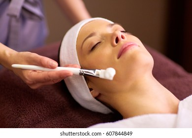 people, beauty, cosmetology and treatment concept - close up of beautiful young woman lying with closed eyes and cosmetologist applying facial mask by brush at spa