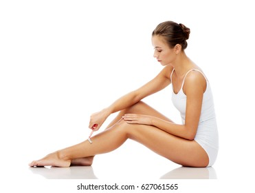 people, beauty, depilation and bodycare concept - beautiful woman with safety razor shaving legs sitting on floor over white background