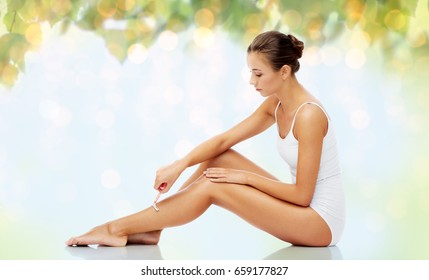 people, beauty and hair removal concept - beautiful woman with safety razor shaving legs sitting on floor over natural green background and lights