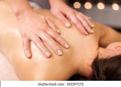 people, beauty, healthy lifestyle and relaxation concept - close up of beautiful young woman lying and having back massage at spa
