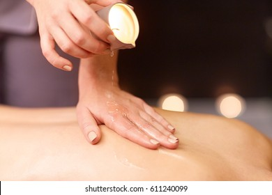 people, beauty, healthy lifestyle and relaxation concept - woman doing back massage with hot oil at spa