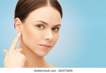 people, beauty, hearing and healthcare concept - face of beautiful woman touching her ear over blue background