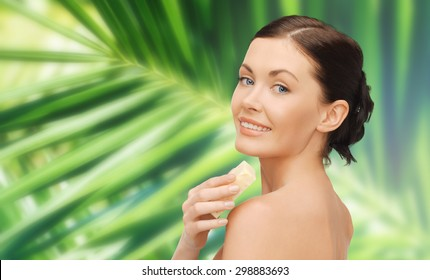 people, beauty, hygiene and summer concept - beautiful woman with soap bar over green palm leaf background