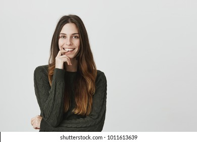People, beauty and lifestyle concept. Attractive good-looking beautiful young woman wearing casual clothes, smiles being pleased to see results of her work. Joyful nice female posing indoors