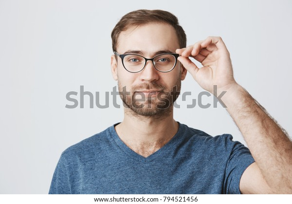 People, beauty and lifestyle concept. Attractive good-looking bearded man wearing stylish spectacles and blue t-shirt, slightly smiles being pleased to see results of his work. Joyful nice male